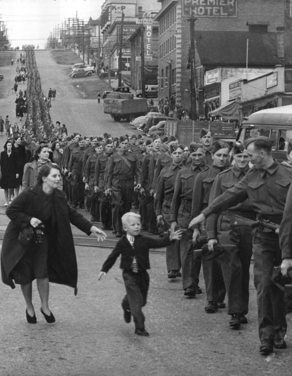 Young Warren Bernard reaches out for one last goodbye to his dad, Jack Bernard, as the BC Regiment Duke of Connaught's Own Rifles, marches down 8th Street, New Westminster, October 1, 1940. C.D. Dettloff photo. Courtesy Vancouver Archives.